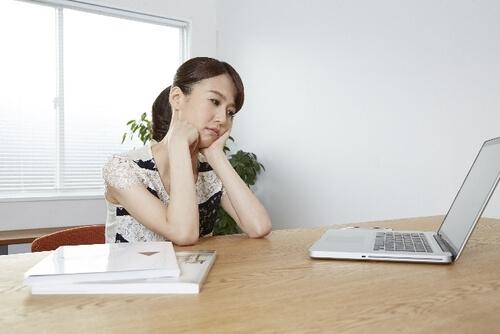 パソコンを前に考え込む女性